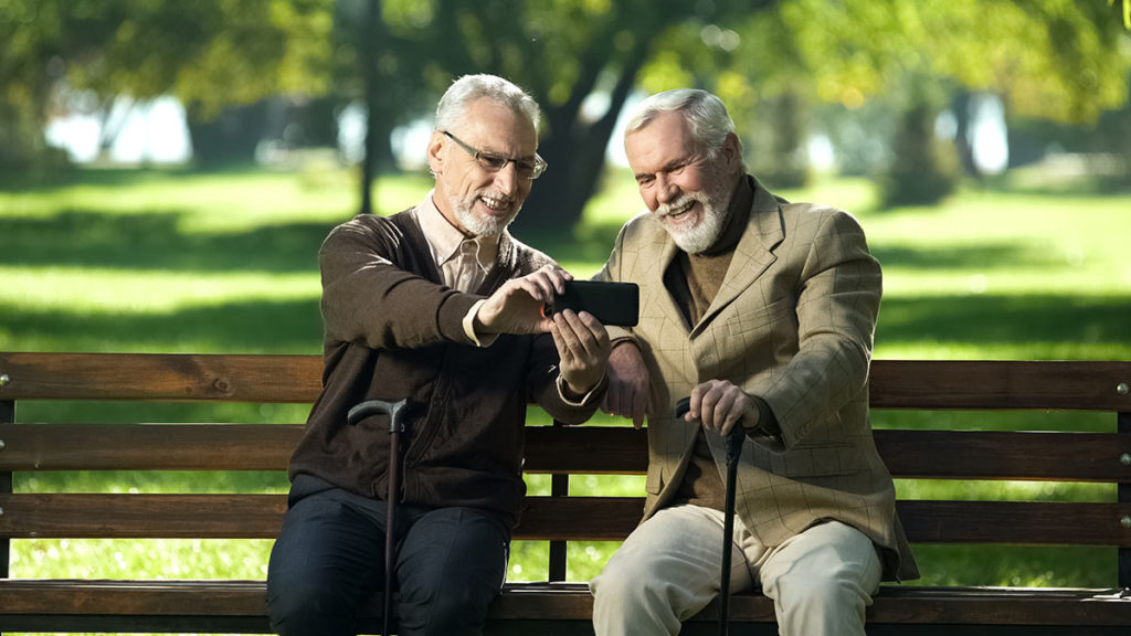 two elderly men sitting on bench looking at phone